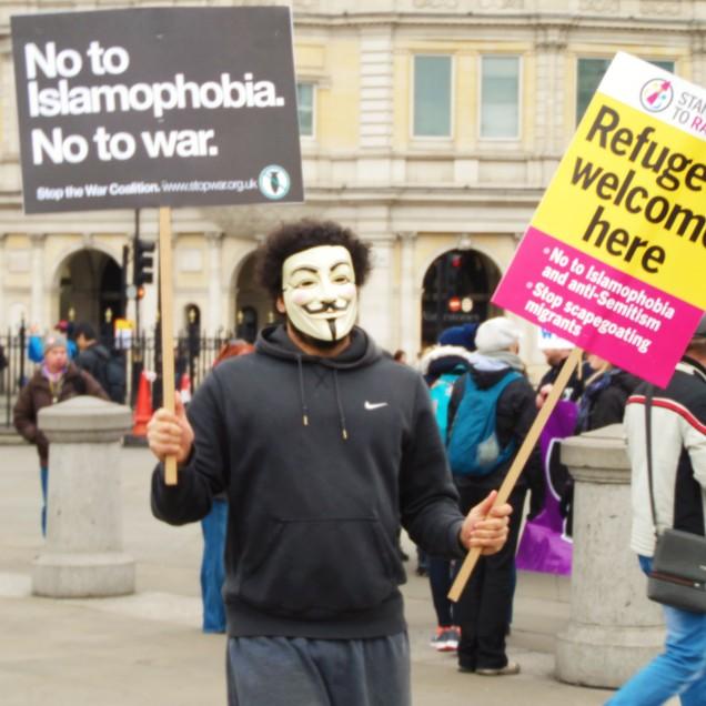"""Un manifestante esibisce la maschera di """"V per Vendetta"""""""