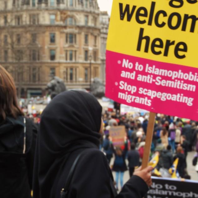 """Una giovane manifestante mussulmana esibisce i cartelli diffusi dagli organizzatori a favore delle porte aperte ai rifugiati, contro """"Islamofobia"""" e """"antisemitismo"""""""